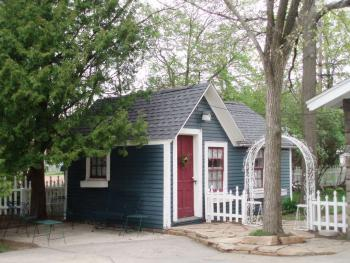Child's playhouse built pre-1901, located next to parking area.