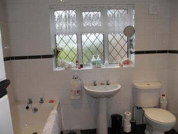 Bathroom for the Garden Room with bath, shower, washbasin, toilet, & luxury toiletries
