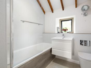 Fort View - full size bath with overhead shower, tall heated towel rail, shaving mirror and vanity unit.