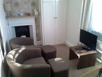 Guest room seating area with Smart TV and original Victorian fireplace.