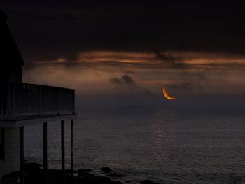 A Crescent Moon Over The Ocean Seen At The Inn