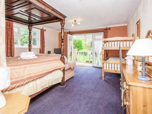 Room 13 , A large family room with a set of bunk beds and a kingsize four poster bed.