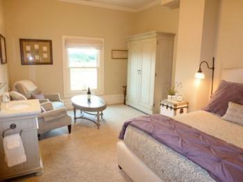 The Emma Room with south facing vineyard views in soft plum and neutral tones. Private bath with shower.