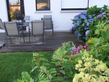 La terrasse privative de la maison de vacances de 110 m² avec son salon de jardin; vue sur de beaux hortensias