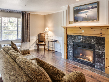 Grand Suite Living Room with Gas Fireplace, Flatscreen Television, Sofa, Dining Table with Chairs, Mini Refrigerator, Microwave and Coffeemaker.