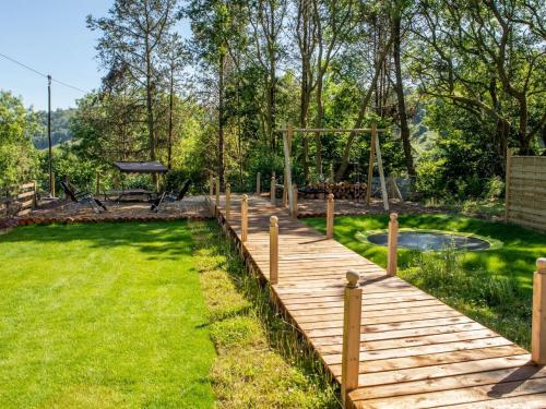 Garden with boardwalk, children's playground including trampoline, swings and zip wire
