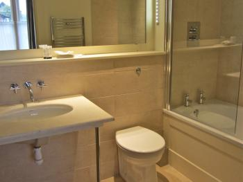 An en-suite bathroom with bath/shower, heated towel rail and shaver sockets.
