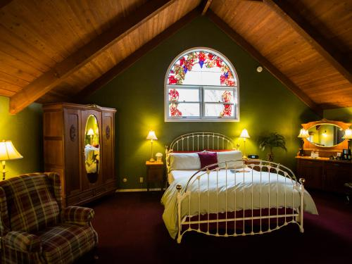 The West Loft with 18 foot vaulted redwood ceilings and handmade stained glass window above the King bed.