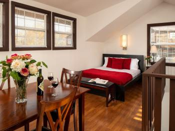 Rosewood Chalet loft with a queen size bed and dining room table and half bathroom overlooking the living room.