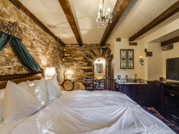 Olde Rose Suite King bed adorned with silk curtains and a crystal chandelier dangling from above. Rustic Romantic Charm with Stone thruout, Wetbar with Copper sink, Electric Fireplace, Flatscreen TV.