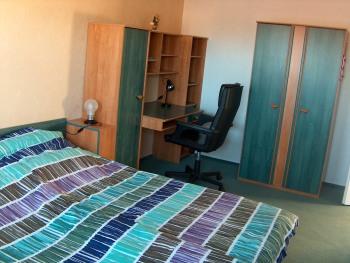 Der Schreibtisch mit vielen Flyern und Karten zu beliebten Ausflugszielen steht im größeren Schlafzimmer neben dem Doppelbett