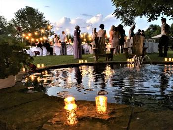 Wedding Reception in Heartstone Lodge courtyard by fish pond & grapevine covered pergola