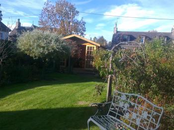 A view of rear garden with log cabin