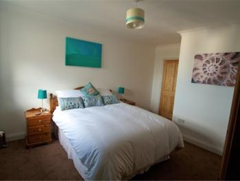 Master bedroom with king size bed, en suite bathroom and sea views