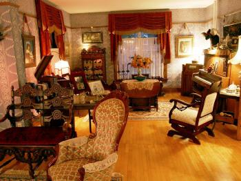 First floor parlors featuring period antiques and a piano with history.