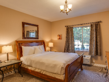Rustic Chic Suite Bedroom with Pillowtop Queen Bed dressed in Luxurious Linens and Down Comforter. Bedroom also features a flatscreen television, alarm clock and closet.