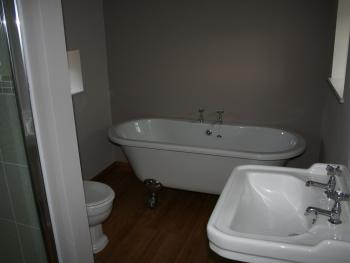 Groom's Ensuite Bathroom with roll top bath and separate shower