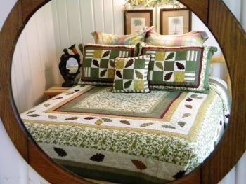 Carriage house suite 1 pine log queen bed with fall bedding.  The decor/bedding in suites is changed seasonally.