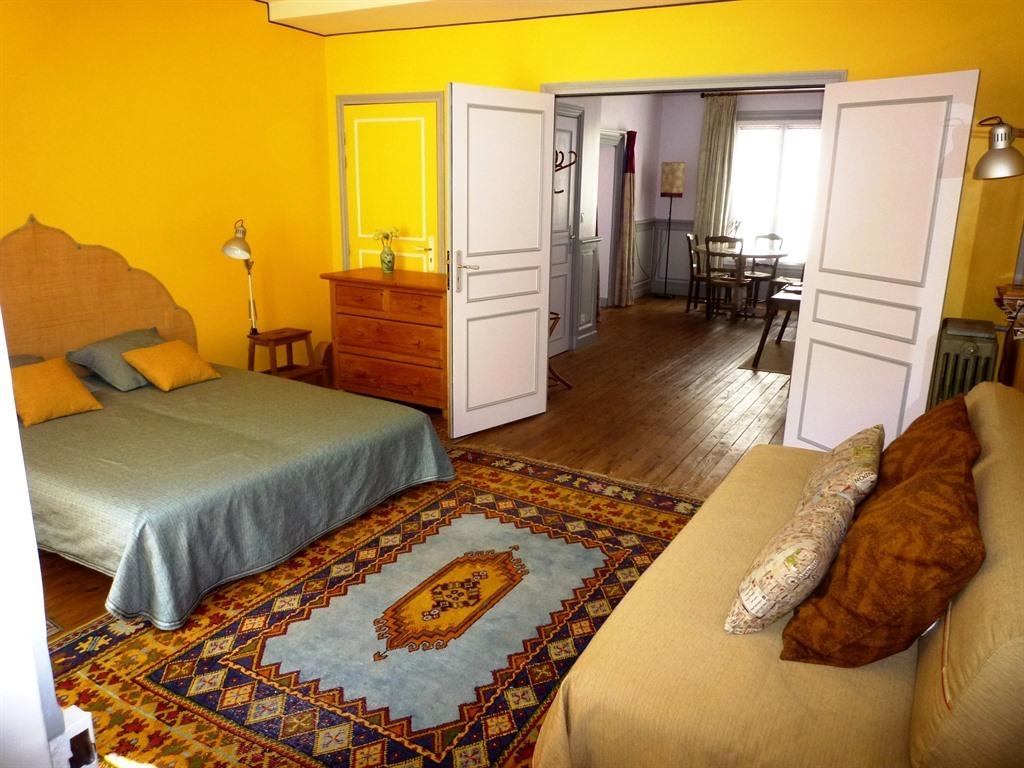La chambre, portes ouvertes sur le salon-salle à manger
