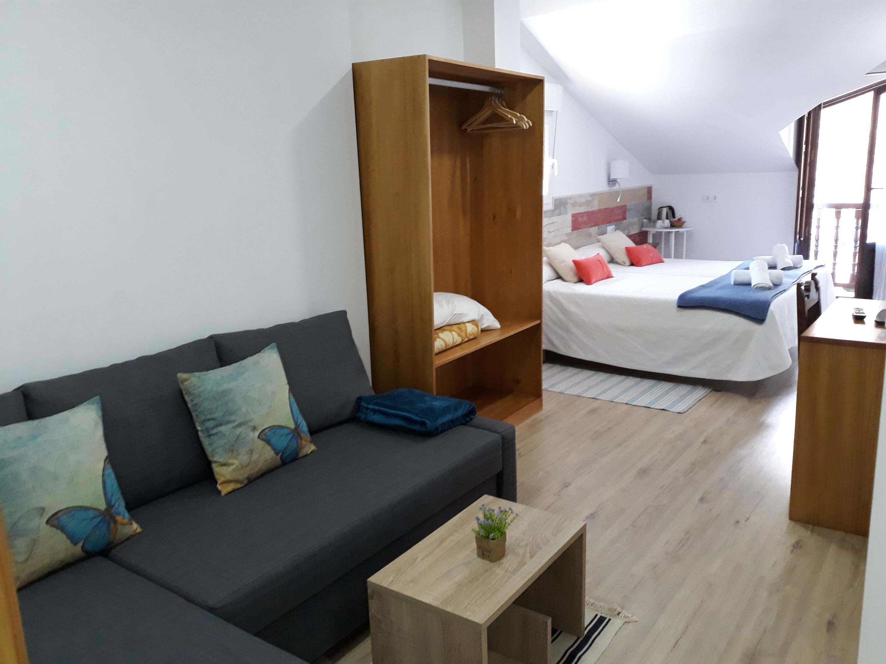 Habitacion con 2 camas y  sofa