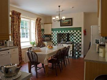 Country Kitchen with large breakfast table and range cooker in the Coastal House