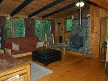 Stepping Stone Totem - view of living room with 2 futon beds, stone fireplace, wall of windows facing the stream
