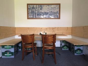 Unter einem traditionellen ostfriesischen Fliesenbild kann man gemütlich sitzen und frühstücken