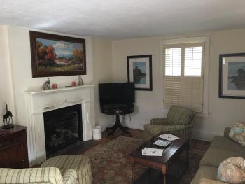 The Garden House Living Room provides a space for cottage guests to unwind with gas fireplace, TV, and free wifi.