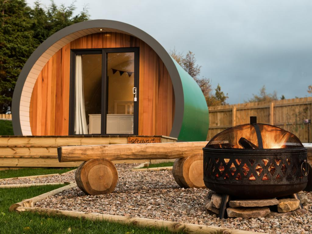 Luxury glamping pods and campfire