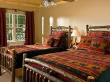"""Our """"Standard Double with Twin""""; a double size bed and a twin size bed are in this room with a walk-out back porch."""