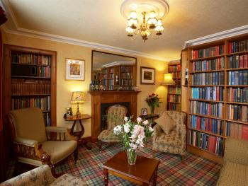 Cosy book-lined lounge and wood burning stove [in Winter]