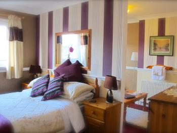 Room 8 a spacious bedroom with adjoining TV room and guest bed..