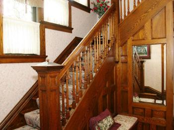 Formal staircase featuring leaded glass stair step windows.