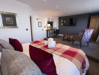 """The Sea View Penhouse Suite. features super kinsize bed, lounge area, stunning sea views, 55"""" smart TV and 26sq m space!"""